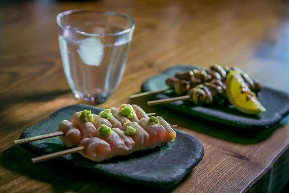 Pickled Raw Chicken, left, and the Chicken Heart skewers with a glass of Shochu at Ippuku in Berkeley, Calif., is seen on April 24th, 2016.