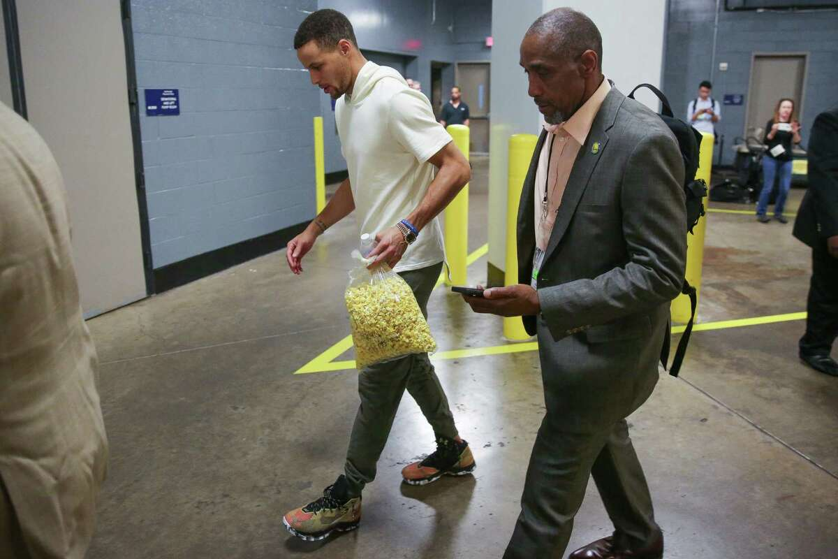In this Sunday, April 24, 2016 photo, Golden State Warriors guard Stephen Curry carries popcorn as he limps out of the Toyota Center after Game 4 in the first round of the NBA playoff series against the Houston Rockets, in Houston. Golden State's record-setting run toward a second consecutive NBA championship may come down to an MRI on the sprained right knee of Stephen Curry. The NBA's reigning MVP missed the second half of a win over the Houston Rockets in Game 4 on Sunday and was expected to have the medical test later Monday. (Karen Warren/Houston Chronicle via AP) MANDATORY CREDIT