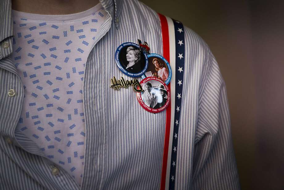 An attendee wears pins in support of Hillary Clinton. Photo: John Taggart, Bloomberg