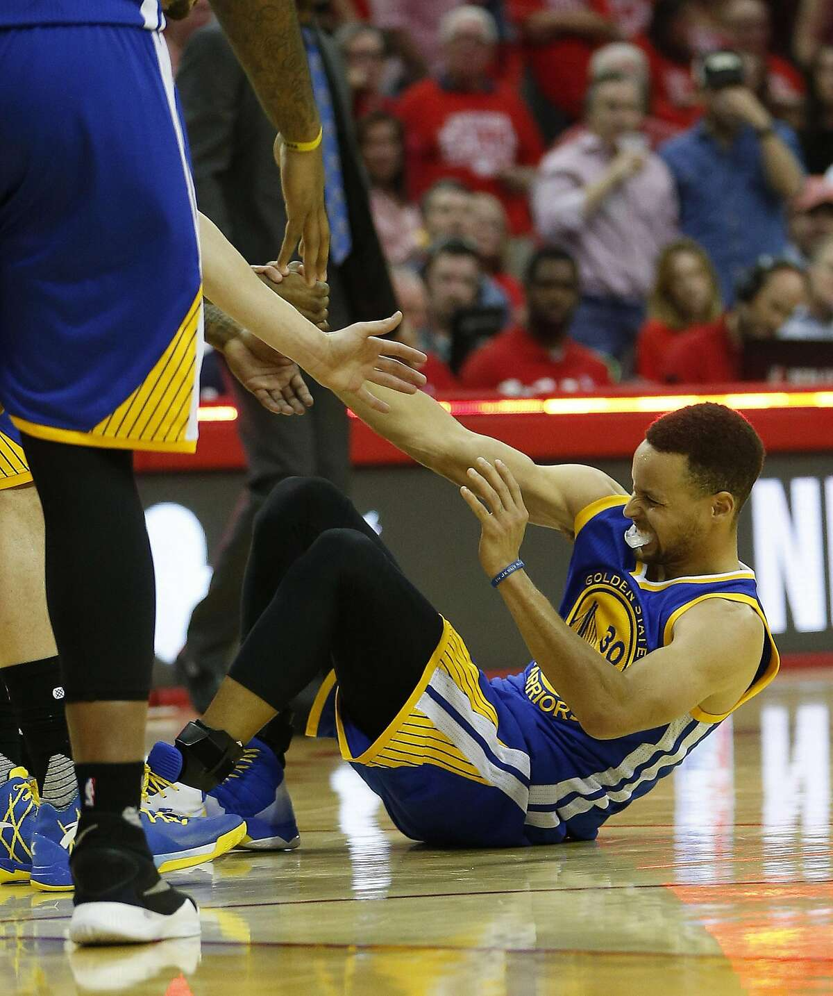 In this Sunday, April 24, 2016 photo, Golden State Warriors guard Stephen Curry (30) is helped up after being injured on the final play during the first half of Game 4 in the first round of the NBA playoff series against the Houston Rockets, in Houston. Golden State's record-setting run toward a second consecutive NBA championship may come down to an MRI on the sprained right knee of Stephen Curry. The NBA's reigning MVP missed the second half of a win over the Houston Rockets in Game 4 on Sunday and was expected to have the medical test later Monday. (Karen Warren/Houston Chronicle via AP) MANDATORY CREDIT