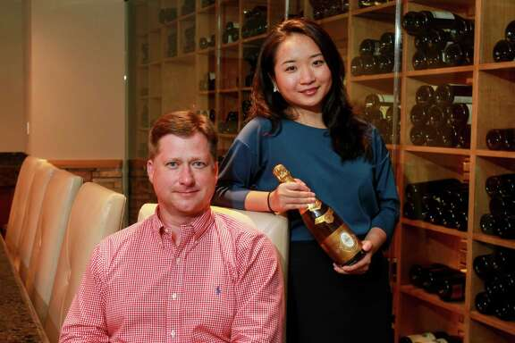 Chris Taylor and Amanda Hu, who is holding a 1988 Cristal Champagne, one of the oldest bottles in the Fred Parks Wine Cellar collection.  (For the Chronicle/Gary Fountain, April 20, 2016)