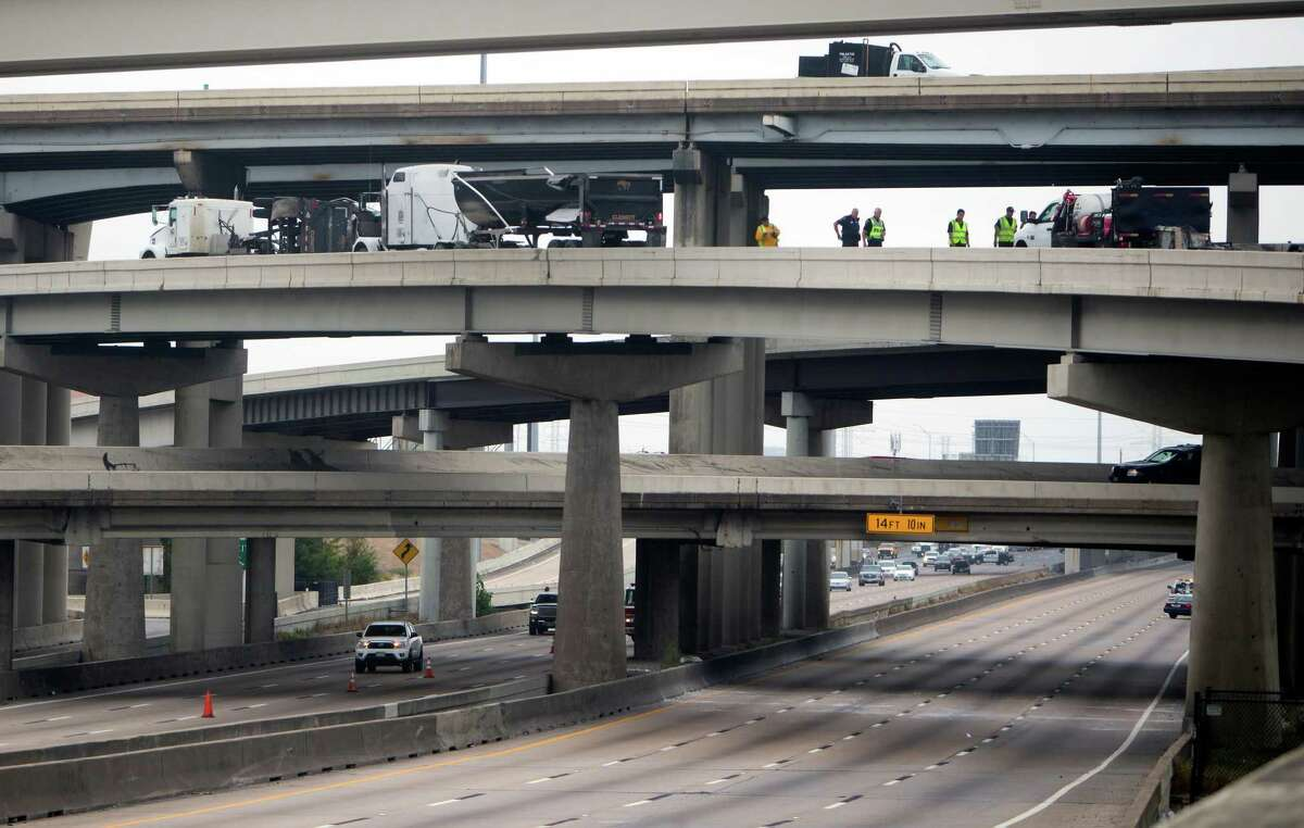 Authorities clean up a wreck on U.S. 59 at the West Loop northbound, Tuesday, Oct. 20, 2015, in Houston. All southbound traffic on U.S. 59 was diverted to the West Loop northbound after a dump truck overturned on an on ramp, dumping debris onto the highway below. According to Houston TranStar, the truck overturned on the ramp from U.S. 59 onto the West Loop southbound, spilling chunks of cement in its bed over the ramp and onto the highway. (Cody Duty / Houston Chronicle)