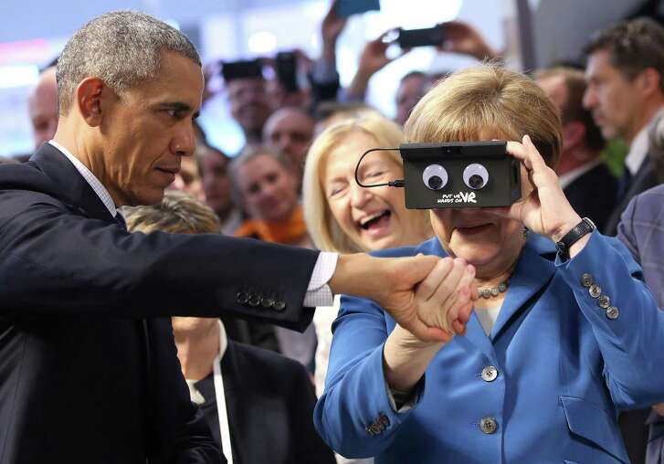 President Obama steadies German Chancellor Angela Merkel as they test virtual reality goggles at the Hannover Messe, an industrial technology trade fair, on Monday in Germany.