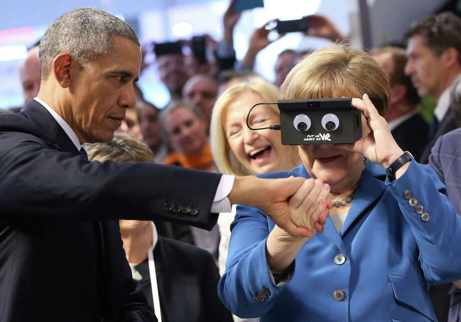 President Obama steadies German Chancellor Angela Merkel as they test virtual reality goggles at the Hannover Messe, an industrial technology trade fair, on Monday in Germany. Photo: Christian Charisius, SUB / dpa