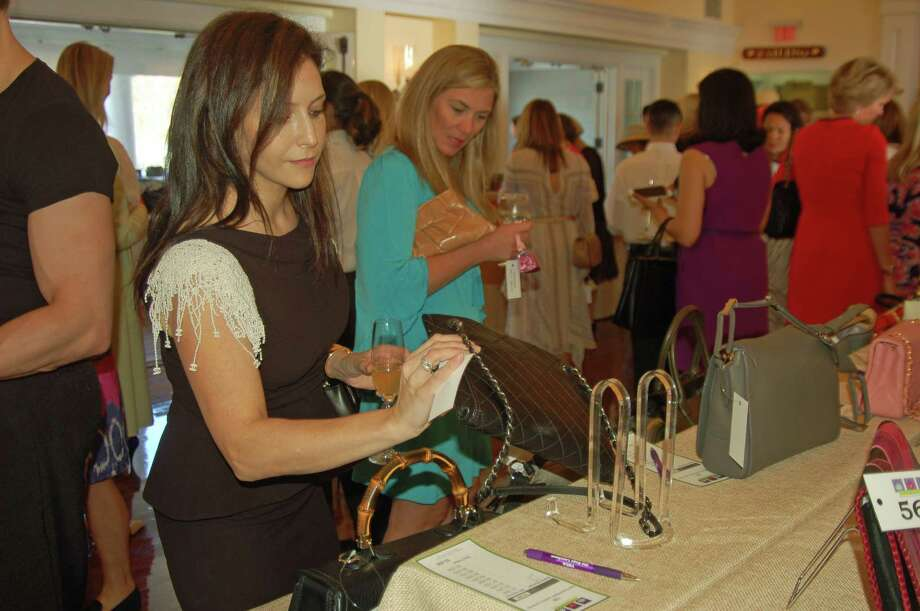 Kim Motola, left, and Kristine Gigliotti check out some of the merchandise up for bid at the 10th annual Old Bags Luncheon at the Belle Haven Club last year. This year's event is set for May 12. Proceeds from the handbag sales go to YWCA Greenwichís Domestic Abuse Services and other YW programs. Photo: Ken Borsuk / Ken Borsuk / Greenwich Time