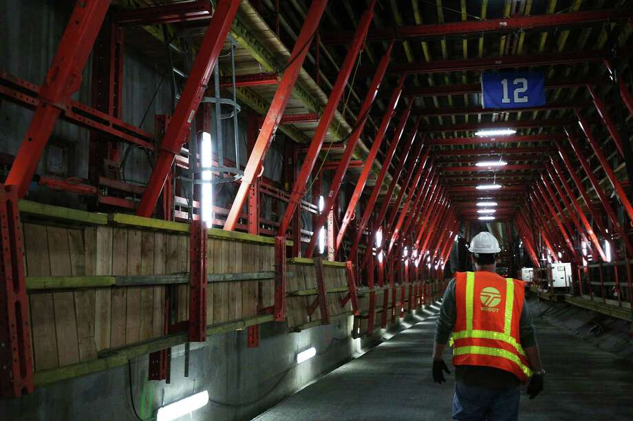 WSDOT tunnel inspector Jay Cooper walks down the Alaskan Way tunnel that has been bored by Bertha over the past three years, Monday, April 25, 2016.  According to WSDOT, there is 1,560 feet of tunnel constructed and 400 feet of roadway completed inside. Beginning Friday, April 29, a section of the Alaskan Way Viaduct will be closed for two weeks as tunneling work continues. Photo: GENNA MARTIN, SEATTLEPI.COM / SEATTLEPI.COM