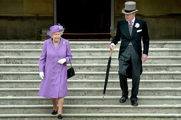 Britain's Queen ELizabeth II, shown here in 2014, carries her black handbag nearly everywhere in public. She even signals her staff with how she positions it.