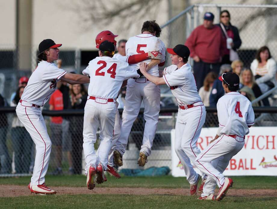 Teammates mob Greenwich's Paul Williams (5) after his walk-off hit in Greenwich's 4-3 win over Trumbull Monday at Greenwich High School. Photo: Tyler Sizemore / Hearst Connecticut Media / Greenwich Time