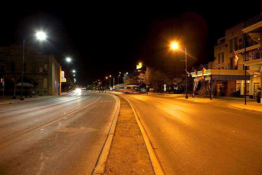 This photo of street lights on South Alamo Street near the Convention Center shows the difference between a LED streetlight (on the left) and an older high-pressure sodium streetlight (at right). Photo: Courtesy /CPS Energy