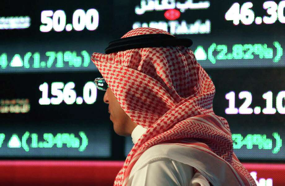 """FILE- In this Monday, June 15, 2015 file photo, a Saudi man walks at the Tadawul Saudi Stock Exchange, in Riyadh, Saudi Arabia. King Salman announced the approval for the """"Vision 2030"""" plan in a short televised announcement on Monday in which he called on Saudis to work together ensure its success. (AP Photo/Hasan Jamali, File) Photo: Hasan Jamali, STR"""
