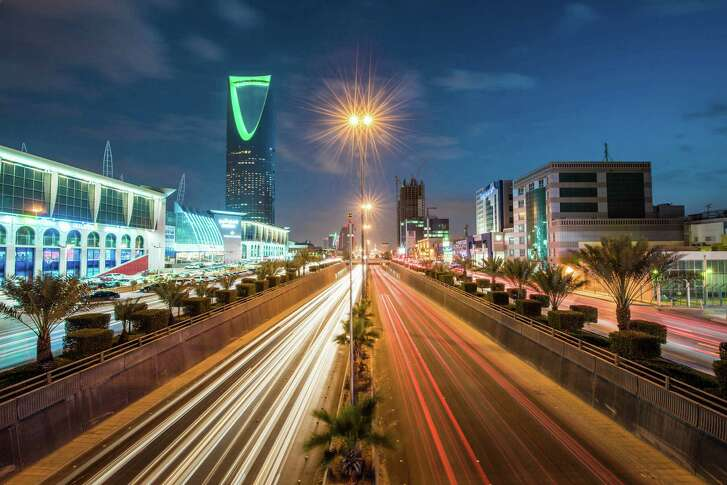 The Kingdom Tower, left, stands alongside the King Fahd highway, illuminated by the light trails of passing traffic, in Riyadh, Saudi Arabia. The nation released a blueprint Monday to reduce its reliance on oil.