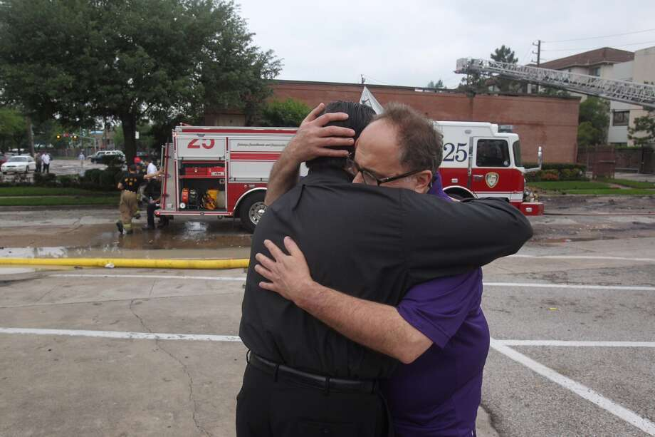 Father Michael J. Lambakis lends support to Cleburne Cafeteria owner George Mickelis after a fire destroyed his restaurant.Photo: Steve Gonzales/Chronicle
