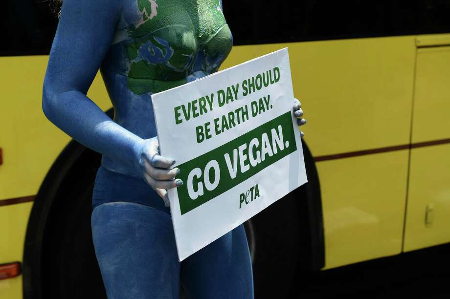 People for the Ethical Treatment of Animals campaigner Ashley Fruno holds a sign encouraging people to go vegan while painted as Mother Earth at a intersection in Bangkok on April 21.  Photo: LILLIAN SUWANRUMPHA, AFP/Getty Images / AFP or licensors