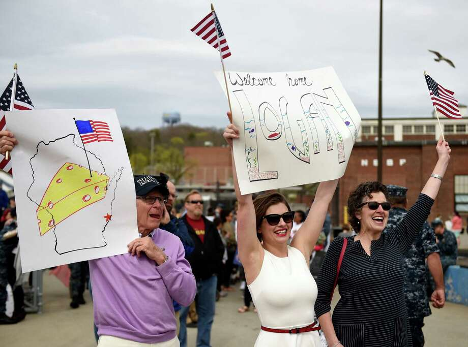 Kelsey McManus, center, flanked by her future in-laws Tom and Ann Roy, waves a banner to attract her fiancee Lt. j.g. Logan Roy as the U.S. Navy submarine USS Toledo (SSN 769) returns to the Navy Submarine Base in Groton, Conn., Monday, April 25, 2016, following a six-month deployment. The Toledo visited ports in Bahrain, France, Spain and Greece.  Photo: Sean D. Elliot, Sean D. Elliot/The Day Via AP / Associated Press