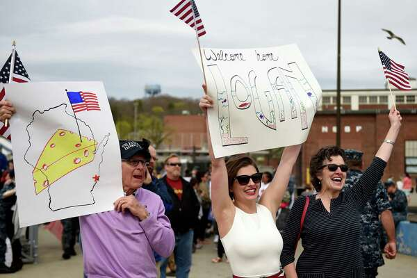 Kelsey McManus, center, flanked by her future in-laws Tom and Ann Roy, waves a banner to attract her fiancee Lt. j.g. Logan Roy as the U.S. Navy submarine USS Toledo (SSN 769) returns to the Navy Submarine Base in Groton, Conn., Monday, April 25, 2016, following a six-month deployment. The Toledo visited ports in Bahrain, France, Spain and Greece. (Sean D. Elliot/The Day via AP)  MANDATORY CREDIT