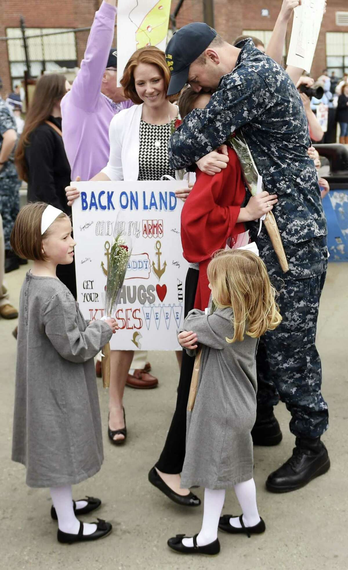 Lt. Cmdr. Jim Henry embraces his daughter Maddie, 13, while daughters Kit, 5, and Harper, 4, and wife Jess, back, look on as the U.S. Navy submarine USS Toledo (SSN 769) returns to the Navy Submarine Base in Groton, Conn., Monday, April 25, 2016, following a six-month deployment. The Toledo visited ports in Bahrain, France, Spain and Greece.