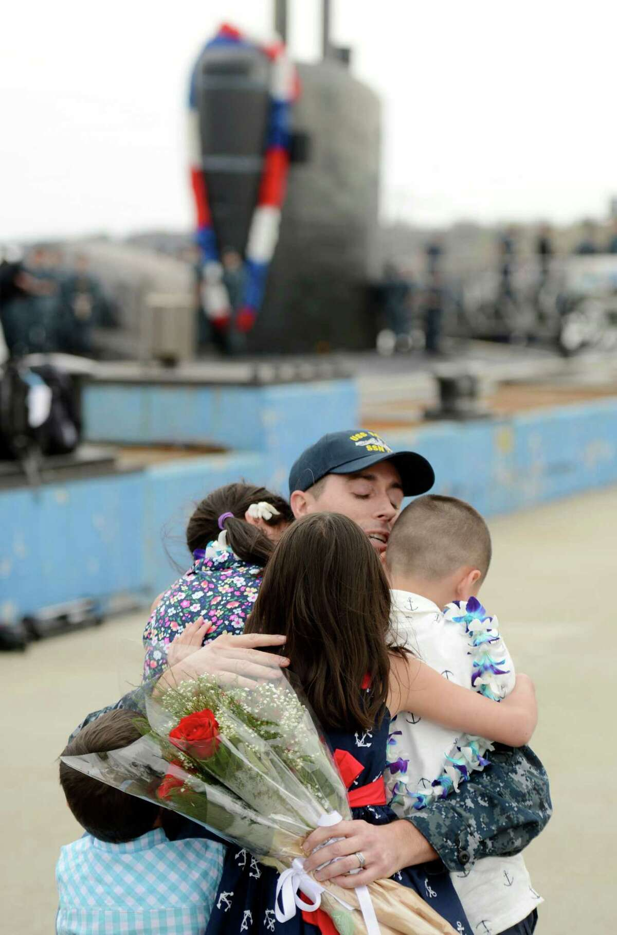 Petty Officer 2nd Class Clint Van de Water hugs his children Elizabeth, 10, Luke, 7, Isabelle, 7, and Jaxon 3, as the U.S. Navy submarine USS Toledo (SSN 769) returns to the Navy Submarine Base in Groton, Conn., Monday, April 25, 2016, following a six-month deployment. The Toledo visited ports in Bahrain, France, Spain and Greece.