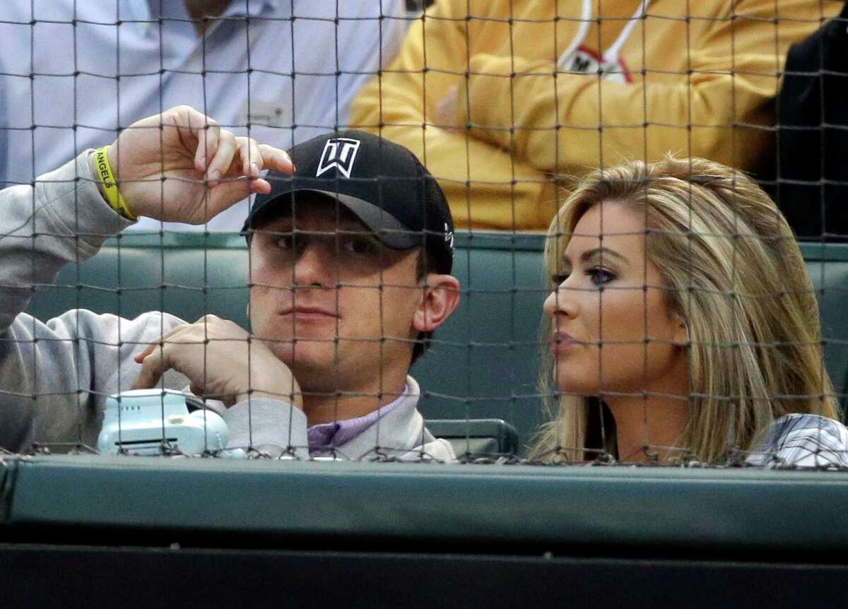 FILE - In this April 14, 2015, file photo, Cleveland Browns quarterback Johnny Manziel, left, sits with Colleen Crowley during a baseball game between the Los Angeles Angels and the Texas Rangers in Arlington, Texas. Prosecutors in Dallas say they will make an announcement Tuesday, April 26, 2016, regarding whether Johnny Manziel has been indicted on allegations that he attacked his ex-girlfriend in January. Brittany Dunn, a spokeswoman for the Dallas County district attorney's office, said Monday that she would not discuss reports from two Dallas television stations, which cited an unnamed source in the DA's office, that Manziel was indicted Thursday. (AP Photo/LM Otero, File)