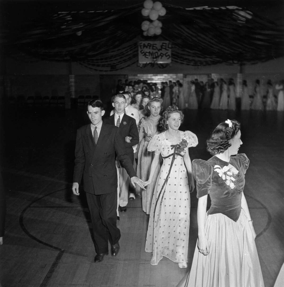 1942: High school seniors cross a gymnasium floor in a double file line at their prom dance, Greenbelt, Maryland.