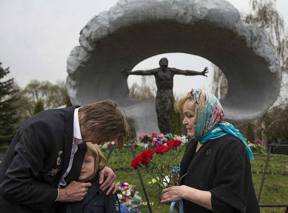 "Alexander Burinin (left), a former ""liquidator,"" his wife, Olga, and grandson, Georgy, visit Mitino Cemetery in Moscow on the anniversary of the explosion. Photo: Pavel Golovkin, Associated Press"