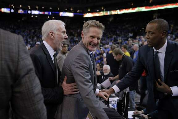 Spurs head coach Gregg Popovich sneaks up on Warriors head coach Steve Kerr before the first half of the Golden State Warriors game against the San Antonio Spurs at Oracle Arena in Oakland, Calif., on Jan. 25, 2016.