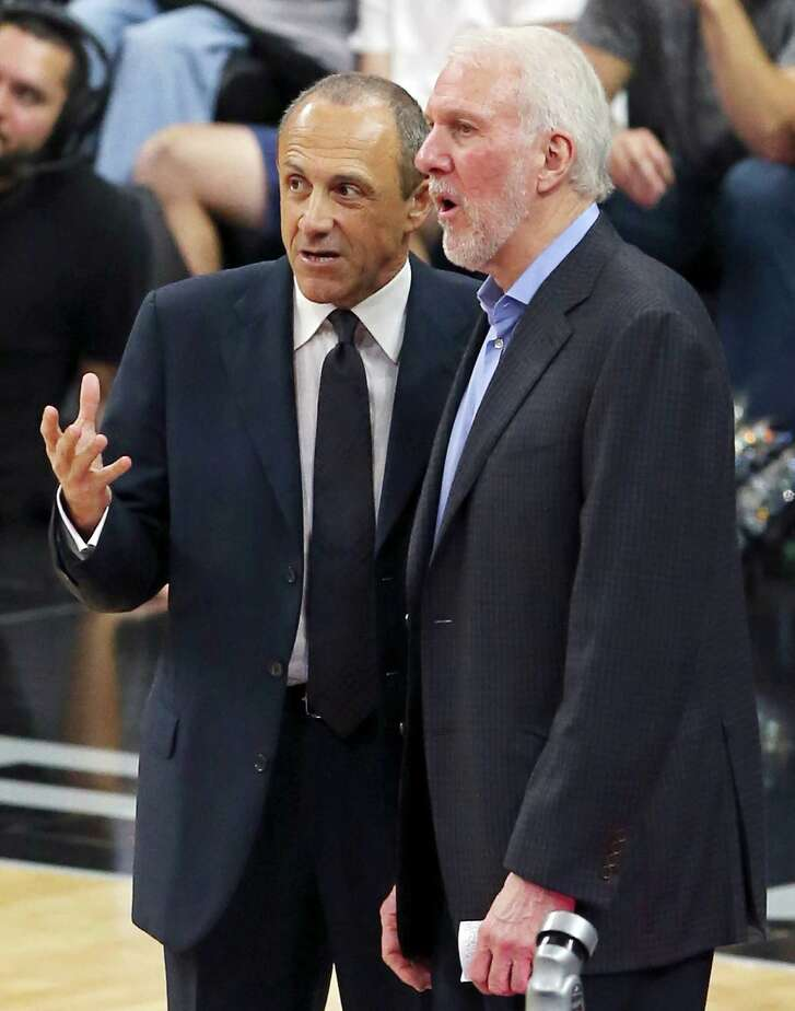 Spurs assistant coach Ettore Messina (left) and head coach Gregg Popovich talk during second half action against the New York Knicks on Jan. 8, 2016 at the AT&T Center.