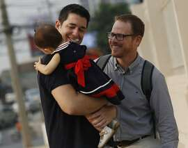 FILE - In this Wednesday, March 23, 2016 file photo, American Gordon Lake, left, and Spaniard Manuel Santos, right, walk with their baby Carmen at the Central Juvenile and Family Court in Bangkok, Thailand. A court in Thailand was to announce its verdict Tuesday, April 26 in a high-profile custody battle between a same-sex couple and a Thai surrogate mother who decided she wanted to keep the baby when she found out they were gay. (AP Photo/Sakchai Lalit, File)