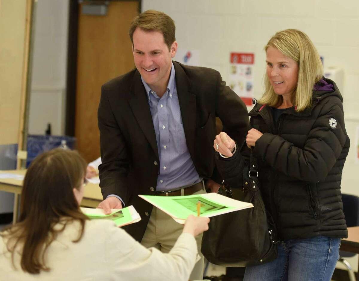 U.S. Rep. Jim Himes and his wife, Mary, check in before voting in the 2016 presidential primary election for Greenwich's District 8 at Central Middle School on Tuesday.