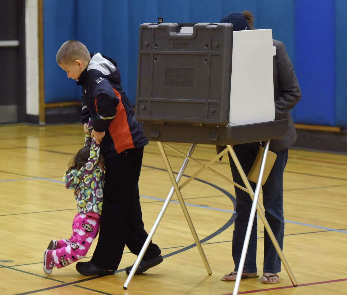Greenwich resident Ludy Nino votes as Tristan, 11, and Connie, 1, play beside her at the 2016 presidential primary election for Greenwich's District 3 at Western Middle School in Greenwich, Conn. Tuesday, April 26, 2016.