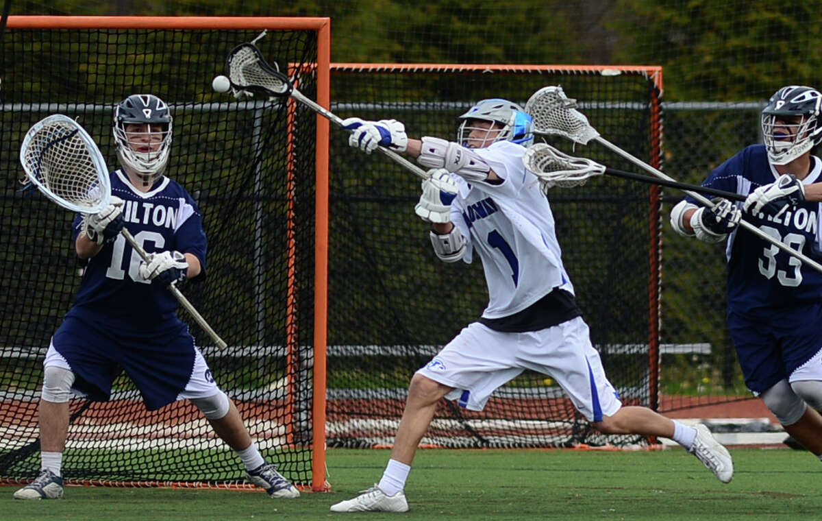 Darien's Brian Minicus (#1) takes a shot on Wilton goalie Andrew Calbrese as Wilton's Tyler Previte (#33) defends during their game on Saturday at Darien High School.