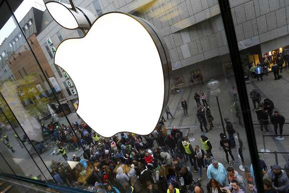 FILE - In this Friday, Sept. 25, 2015, file photo, people wait in front of the Apple store in Munich, before the worldwide launch of the iPhone 6s. On Tuesday, April 26, 2016, Apple reports financial results. (AP Photo/Matthias Schrader, File)
