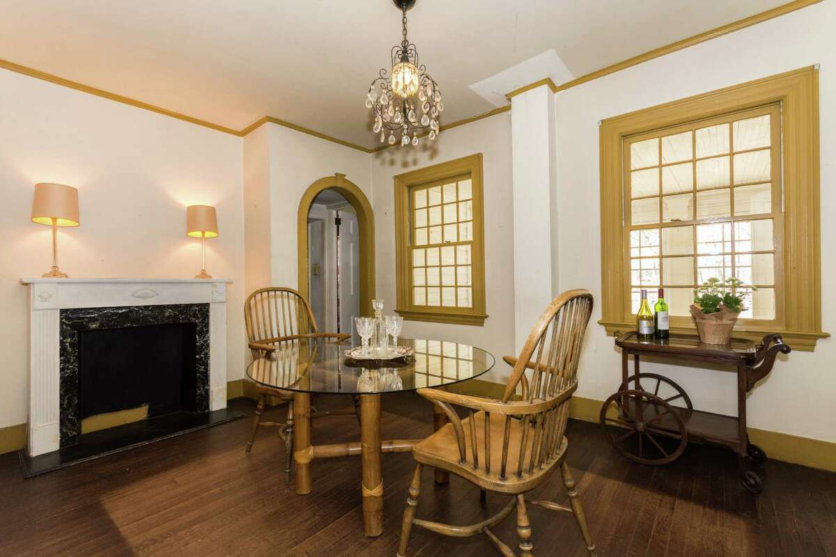 At right of entry is a formal living room with five 12-over-12 windows, a wood burning fireplace with a hand carved mantle and plaster walls with chair rail.