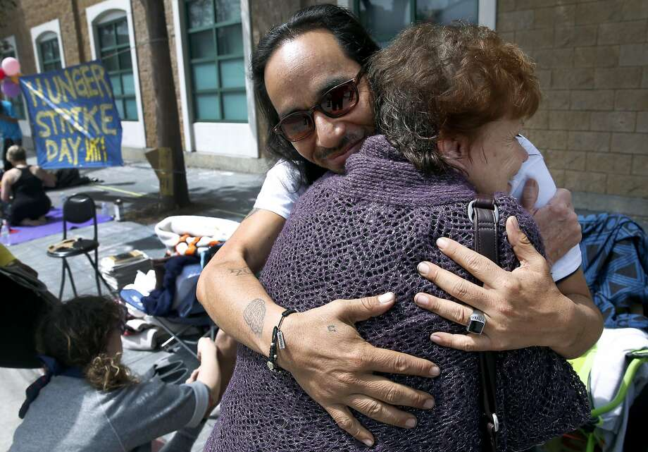 Ilyich Sato, who's known as the rapper Equipto, hugs longtime family friend Naomi White as a hunger strike continues in front of the Mission police station on Valencia Street in San Francisco, Calif. on Tuesday, April 26, 2016. Activists are calling for Chief Greg Suhr to resign after a number of fatal officer involved shootings. Photo: Paul Chinn, The Chronicle