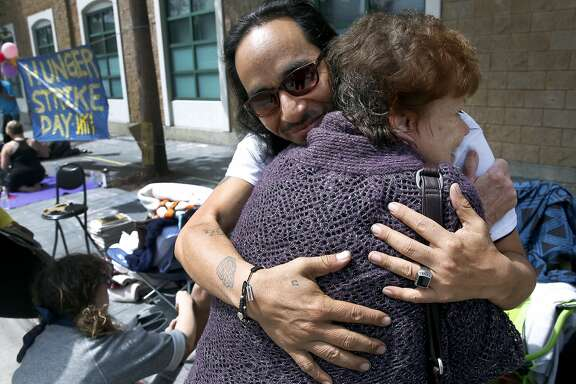 Ilyich Sato, who's known as the rapper Equipto, hugs longtime family friend Naomi White as a hunger strike continues in front of the Mission police station on Valencia Street in San Francisco, Calif. on Tuesday, April 26, 2016. Activists are calling for Chief Greg Suhr to resign after a number of fatal officer involved shootings.
