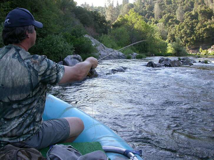 Paul Evans casts for trout with fly rod on Upper Sacramento River on raft trip with guide Jack Trout Photo Tom Stienstra/The Chronicle