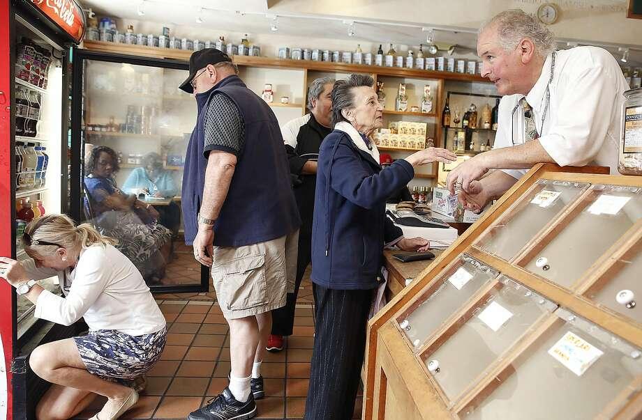 David DeVincenzi (right), son of Genova Deli owner Dominic DeVincenzi, helps customer Mrs. Gasparro, while his wife, Patti, kneels in front of a display case to help Joe Scodella (center), a deli customer since 1956. Photo: Liz Hafalia, The Chronicle