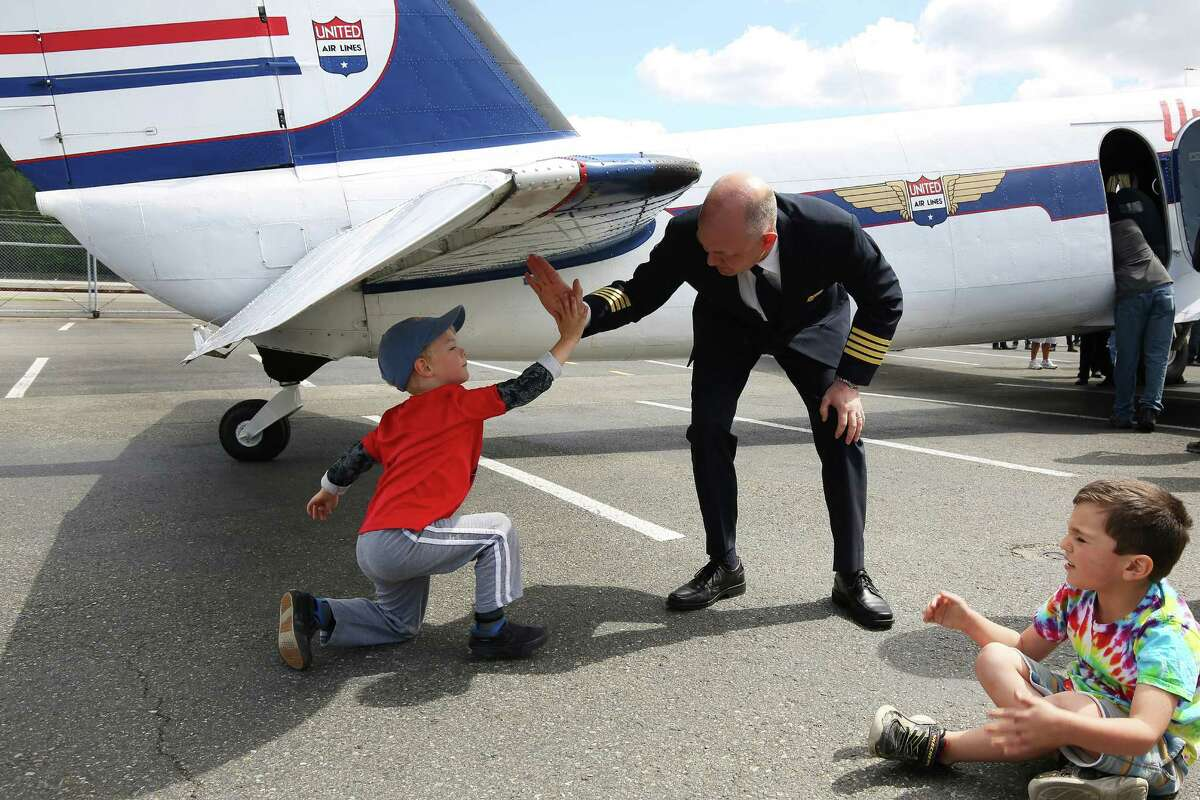 Assistant chief test pilot for Boeing Chad Lundy high-fives Cameron Nichols-Rage after co-piloting the1933 Boeing 247D Airliner's final flight to the Museum of Flight, Tuesday, April 26, 2016. The plane is the oldest flyable Boeing, all-metal airliner. The plane will be on display in front of the museum throughout the summer, before it is placed in the new Aviation Pavilion.