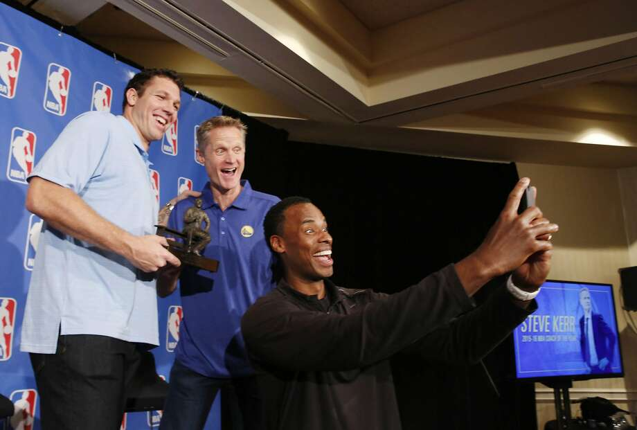 Warriors head coach Steve Kerr (center) holds the  the Red Auerbach Trophy as he takes a photo with Luke Walton (left) , Warriors assistant coach, and Jarron Collins, Warriors assistant coach, during the NBA Coach of the Year press conference on Tuesday, April 26, 2016 in Oakland, California. Photo: Lea Suzuki, The Chronicle