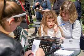 Students participating in the I Wish I Say project type a postcard to one of the presidential candidates as dictated by a mom and daughter in Bryant Park in New York City