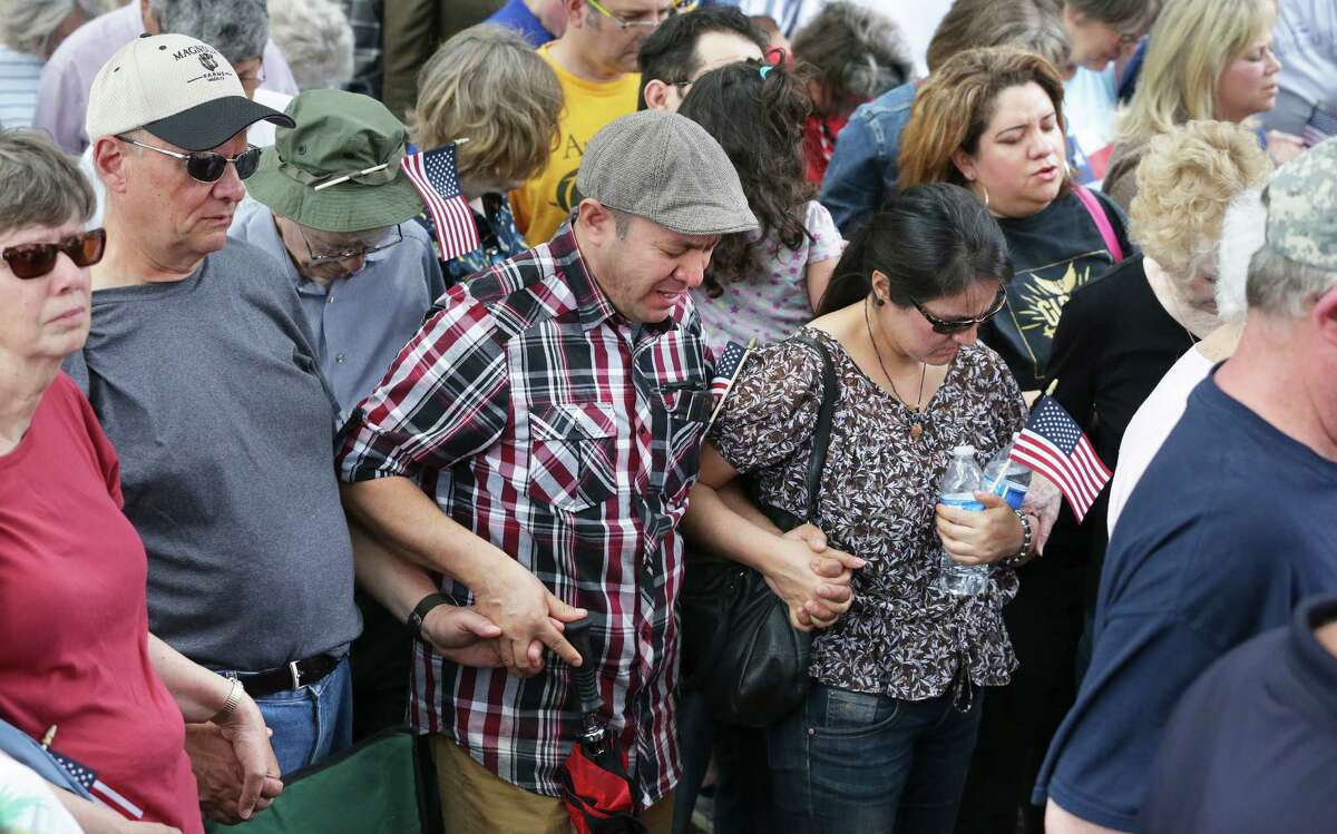 Javier Carrera (center) holds hands with others as he prays for the country as Franklin Graham speaks at a prayer rally attended by Governor Greg Abbott and Lt. Gov. Dan Patrick on April 26, 2016.