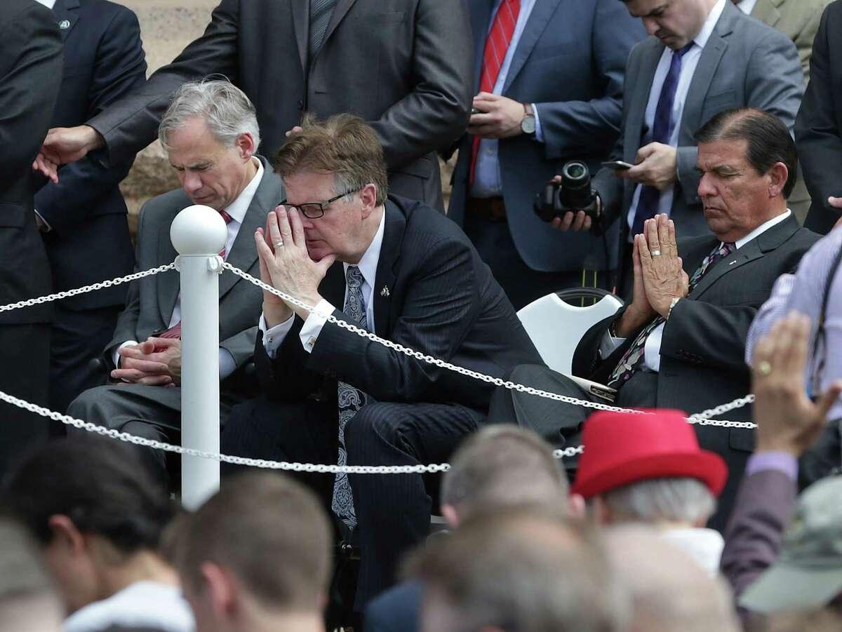 Governor Greg Abbott and Lt. Gov. Dan Patrick pray with Senator Eddie Lucio as Franklin Graham speaks at a prayer rally attended by on April 26, 2016.