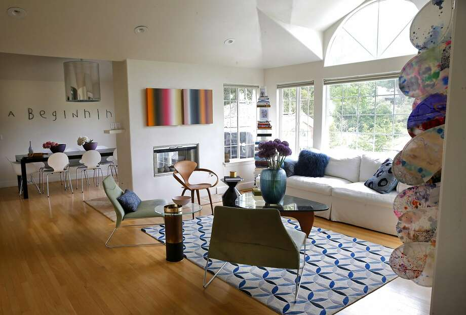 """The living and dining areas of art consultant Alexandra Ray's San Rafael home contains artwork (center) by Patrick Dintino called """"Lush"""" and a Chris M. Miller work (on far right wall), which consists of 140 painted pedals on Japanese Mulberry. Photo: Michael Macor, The Chronicle"""