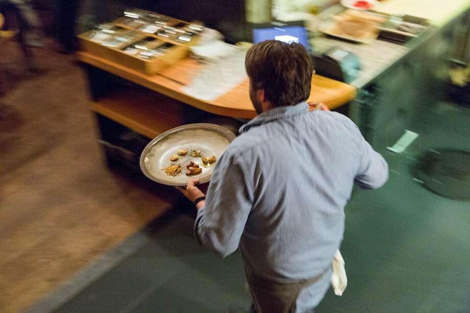 Stuart Brioza runs a dish to a table at the Progress. Photo: Jason Henry, Special To The Chronicle