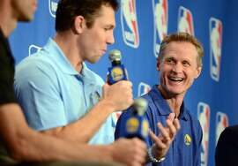 Golden State Warriors head coach Steve Kerr, right, listens as assistant coach Luke Walton addresses the media after Kerr was named the NBA coach of the year, Tuesday, April 26, 2016, in Oakland, Calif. Kerr won the award after leading to the Golden State Warriors to the best regular season record in league history. Kerr got 64 first-place votes from the panel of 130 media members who regularly cover the league. Portland's Terry Stotts was second in relatively close voting. San Antonio's Gregg Popovich was third. (Kristopher Skinner/Oakland Tribune via AP) MANDATORY CREDIT