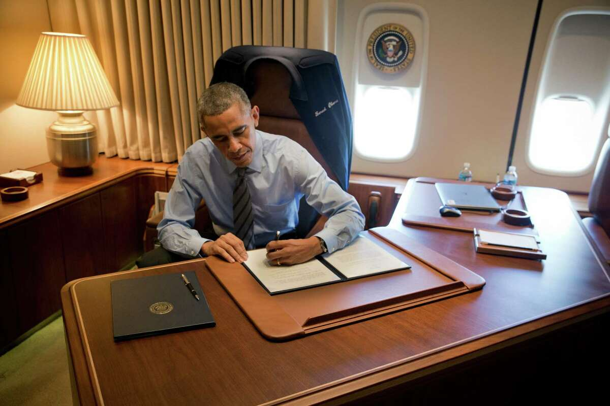 President Barack Obama signs executive actions on immigration while aboard Air Force One in Las Vegas, Nov. 21, 2014. The Supreme Court heard arguments earlier this month challenging Obama's authority to implement a plan that would allow unauthorized immigrants who are parents of citizens or lawful permanent residents to apply for a program sparing them from deportation, and allowing them to work. (Stephen Crowley/The New York Times)