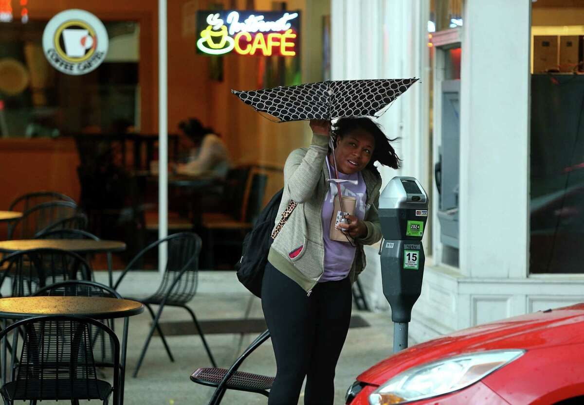 """Nicole Brown of Hazelwood tries to save her umbrella that succumbed to high winds on Tuesday, April 26, 2016, in St. Louis, Mo., as rain from an afternoon storm began to fall. """"I didn't know it was gonna rain like this,"""" she said. (Christian Gooden/St. Louis Post-Dispatch via AP) EDWARDSVILLE INTELLIGENCER OUT; THE ALTON TELEGRAPH OUT; MANDATORY CREDIT"""
