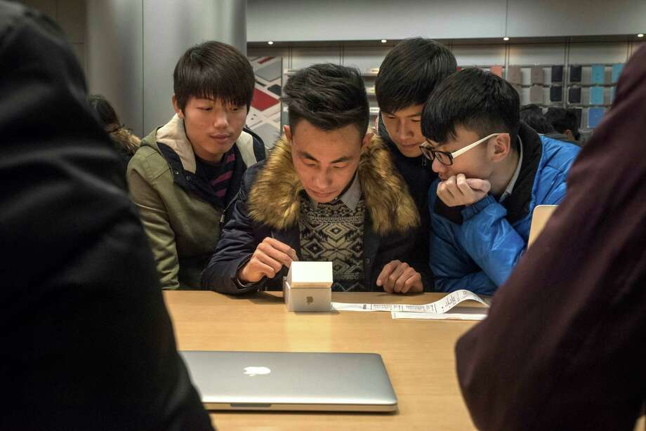 An owner of a new iPhone sets it up as friends gather  last year at an Apple store in Beijing.  Photo: GILLES SABRIE, STR / NYTNS