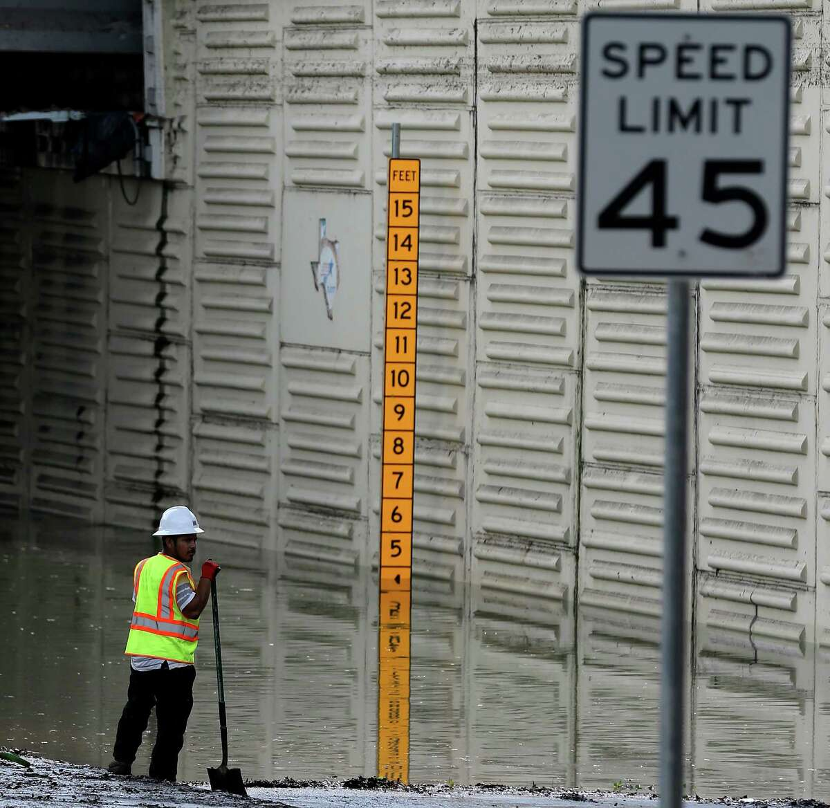 Road crew workers remove debris and water off of an exit ramp at Loop 610 and Hardy Tollway on April 19, one day after flooding there turned deadly.