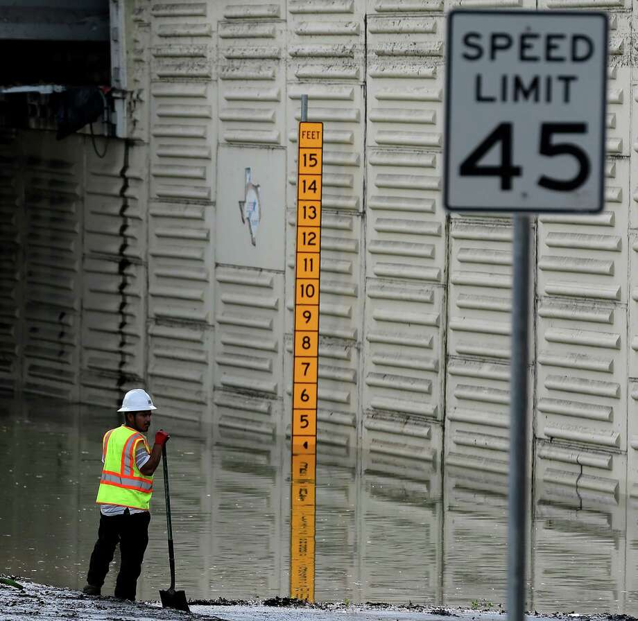 Road crew workers remove debris and water off of an exit ramp at Loop 610 and Hardy Tollway on April 19, one day after flooding there turned deadly. Photo: Elizabeth Conley, Staff / © 2016 Houston Chronicle