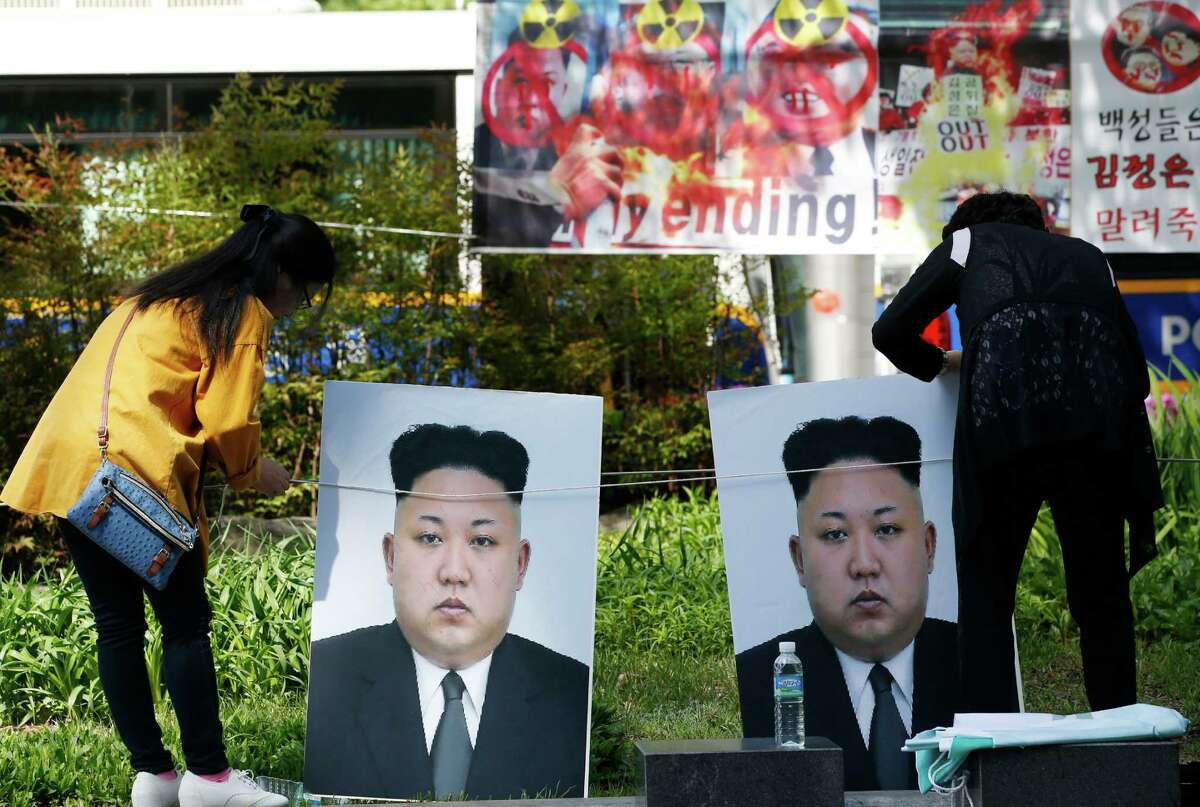 Participants set the portraits of North Korean leader Kim Jong Un during a rally denouncing North Korea's nuclear test and missiles and North Korea's female military human rights in Seoul, South Korea, Tuesday, April 26, 2016. The rally is a part of an annual event called North Korea Freedom Week which held from April 24-30. North Korea is believed to have placed a new, powerful mid-range missile on standby for an impending launch, a news report said Tuesday. (AP Photo/Lee Jin-man)